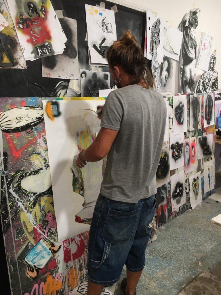 Mart Signed al lavoro spray e stencil art in studio a Livorno